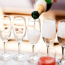 Bottle Of Champaign Being Poured Into A Row Of Champagne Glasses